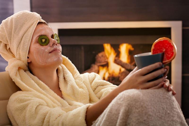 Mädchen sitzt mit Maske auf ihrem Gesicht und kühlt