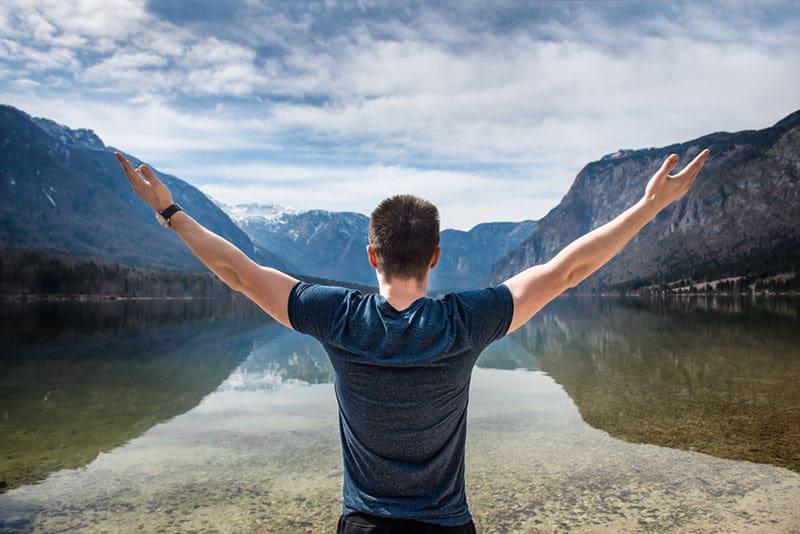 Mann breitete seine Arme vor dem See aus