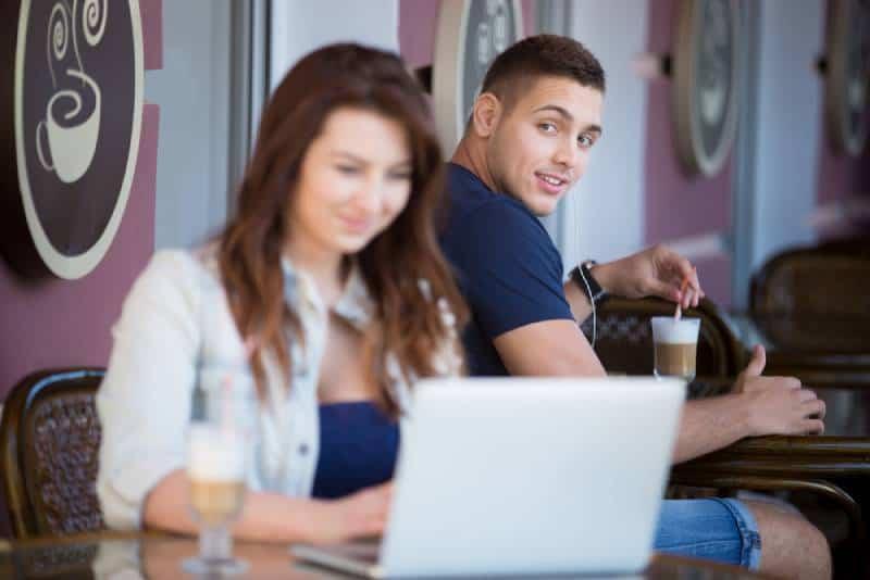 Mann, der Frau betrachtet, während sie auf Laptop tippt