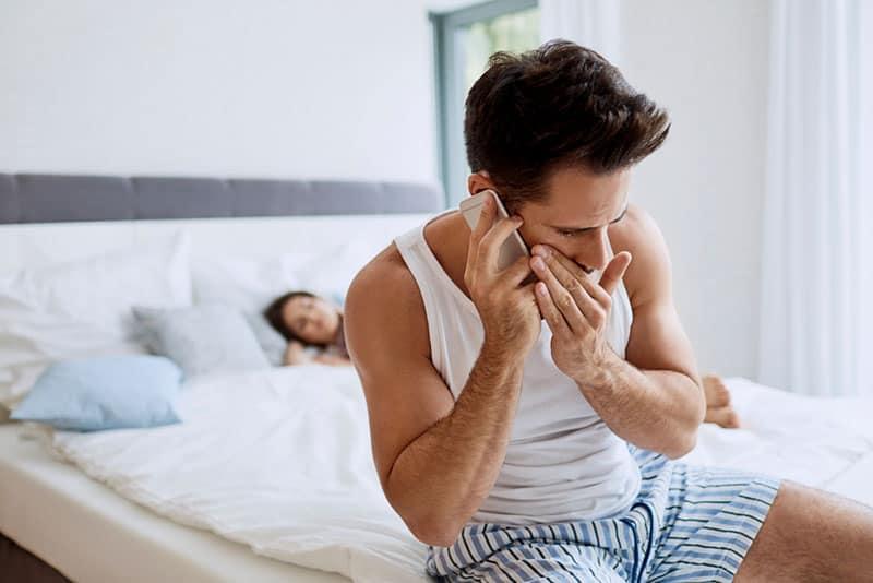 Mann, der im Schlafzimmer am Telefon spricht