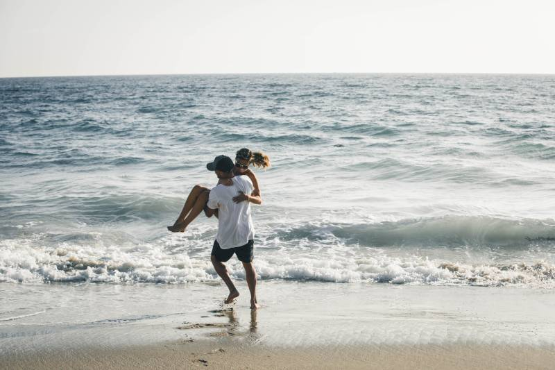 Mann hält seine Frau in den Armen am Meer