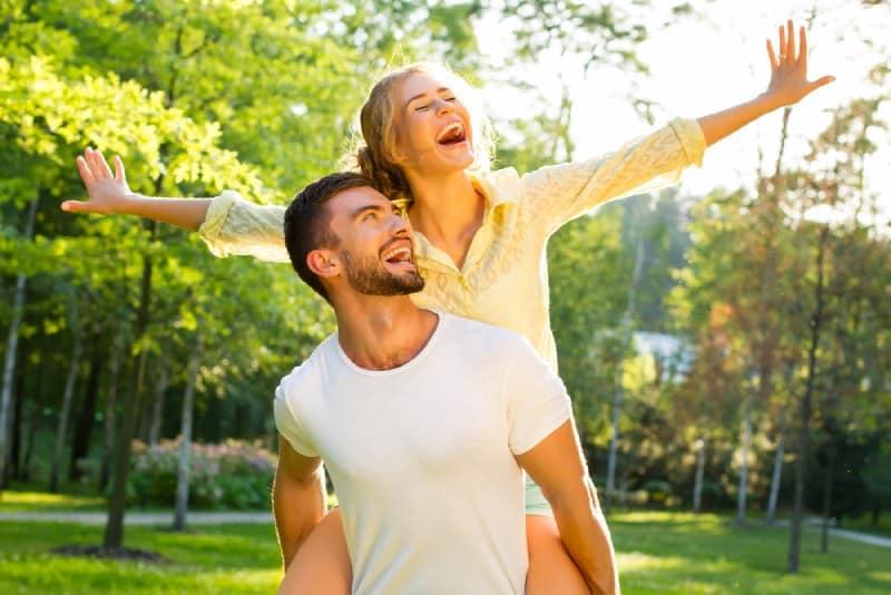 Mann huckepack ihre Freundin draußen auf der Sonne