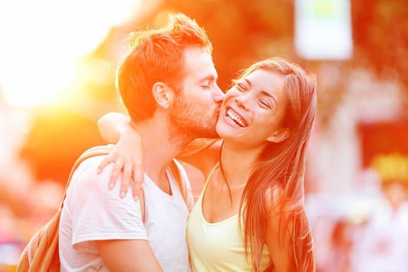 Mann küsste seine lächelnde Freundin draußen