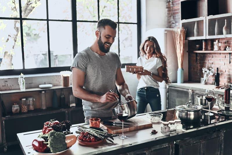 Mann kocht in der Küche mit seiner Freundin
