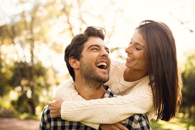 Mann lacht während girll ihn umarmt