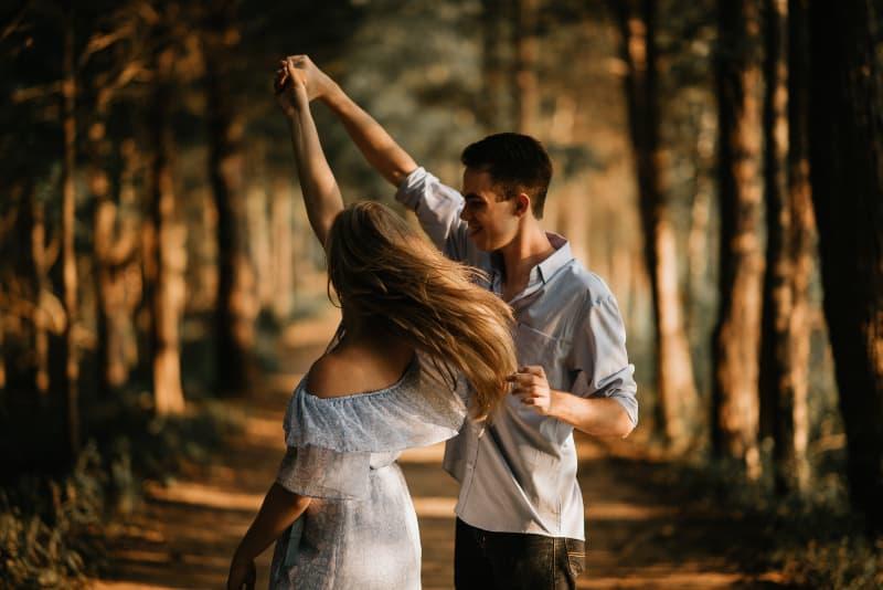 Mann mit Frau, die in der Mitte der Bäume tanzt