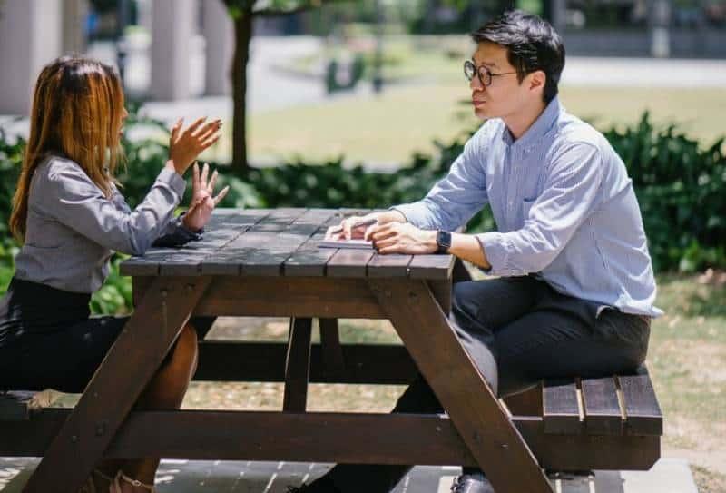 Mann und Frau sprechen draußen auf dem Tisch