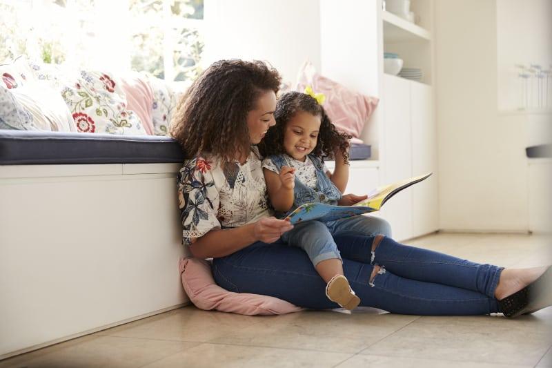 Mutter sitzt auf dem Boden und liest ein Buch