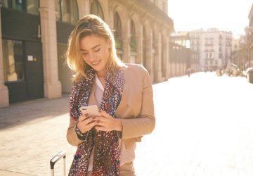 schönes blondes Mädchen, das am Telefon tippt