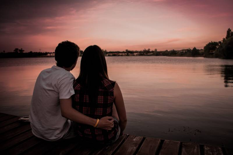 Paar, das am See sitzt