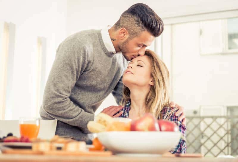 Paar frühstückt mit Frau und küsst sie