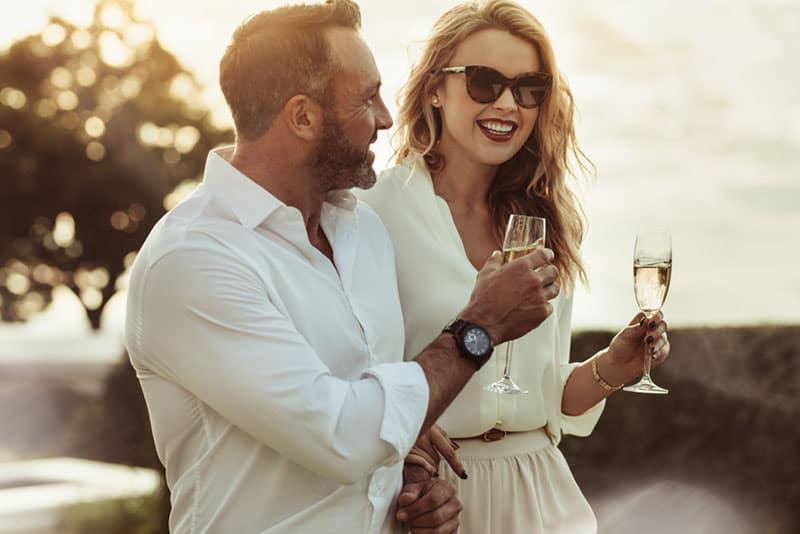 Paar hält einen Champagner und lächelt