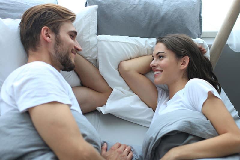 Paar im Bett liegen und reden