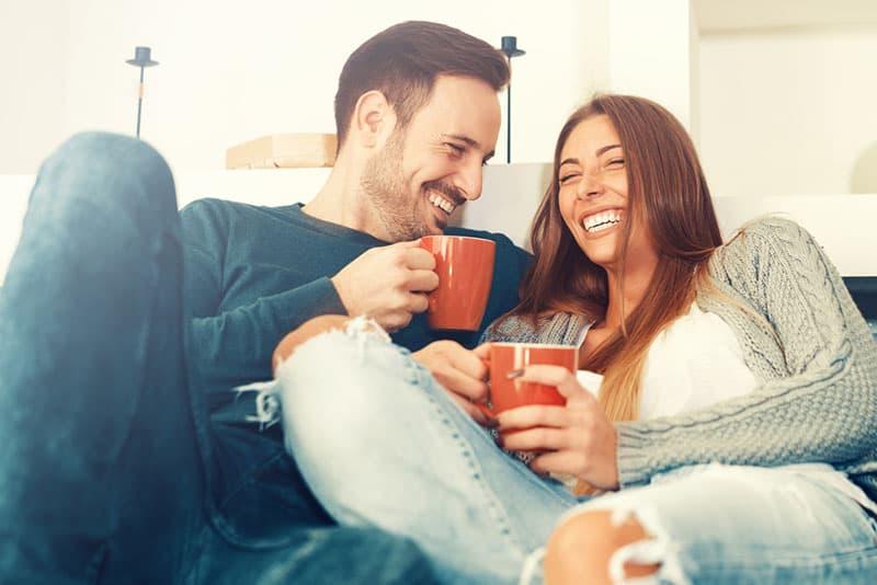 Paar lächelt und trinkt Kaffee