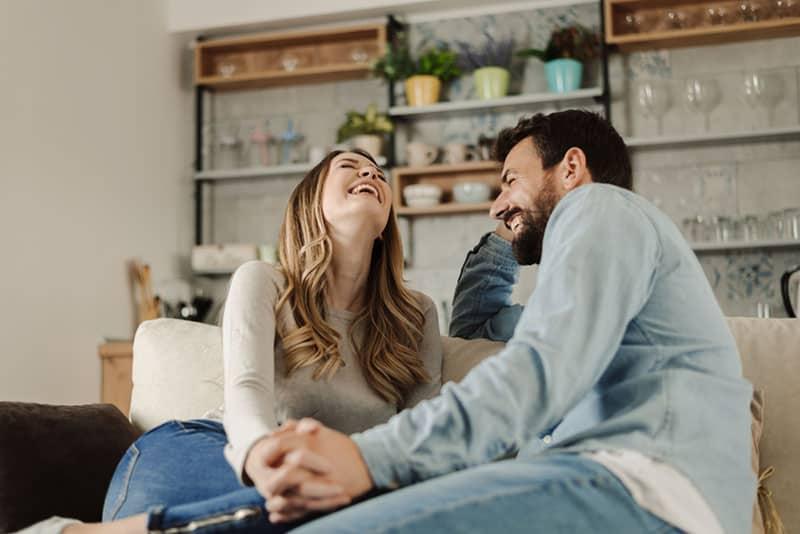 Paar laut auf der Couch lachen
