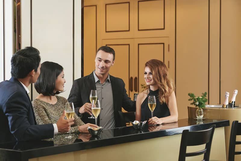 Paar mit Freunden in der Bar vorstellen