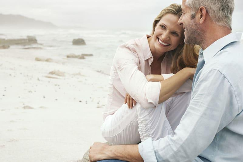 Paar mittleren Alters, das am Strand umarmt