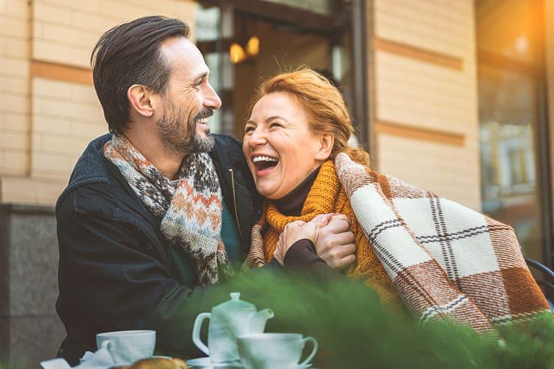 Paar mittleren Alters, das zusammen im Café lächelt