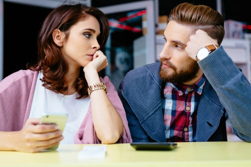 Paar sitzt an der Kaffeebar mit besorgtem Gesicht