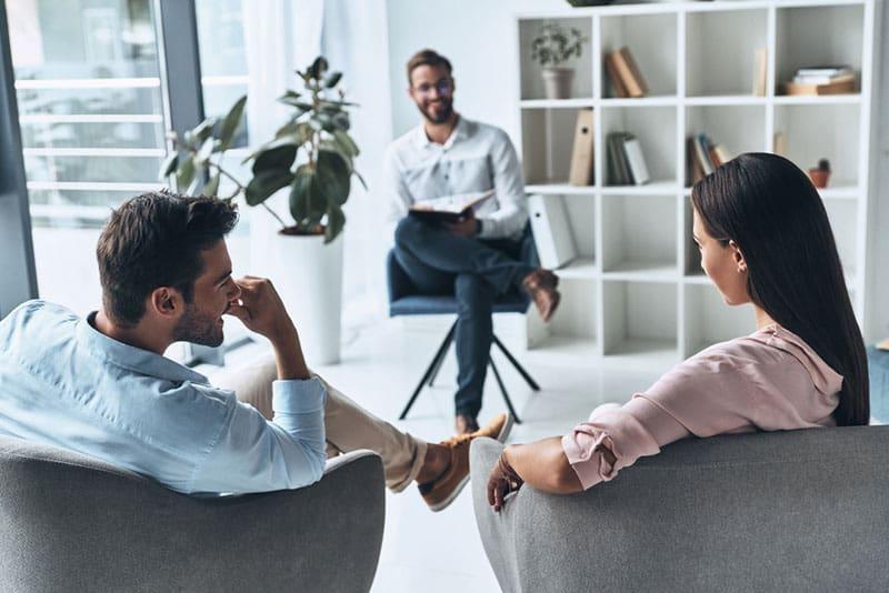 Paar sitzt im Therapiebüro mit Psychologe