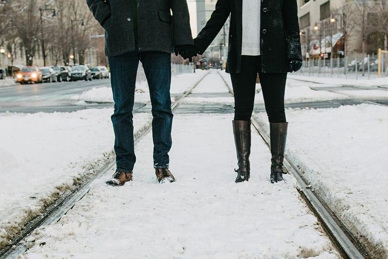 Paar zusammen auf dem Schnee stehen