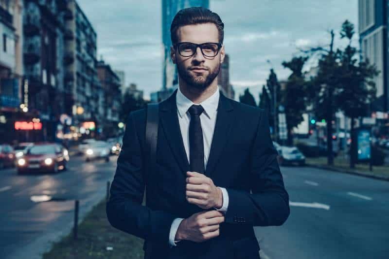Selbstbewusster Mann im vollen Anzug, der seinen Ärmel verstellt und wegschaut, während er draußen steht
