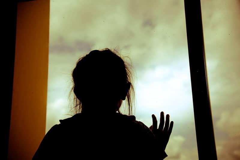 Silhouette der Frau, die Fenster zu Hause hält