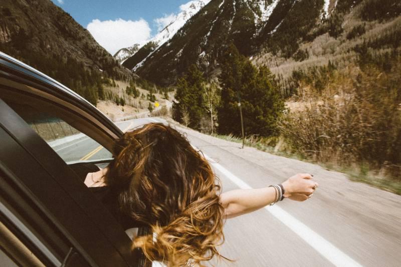 Frau reitet auf Fahrzeug, das ihren Kopf und rechten Arm außerhalb des Fensters setzt