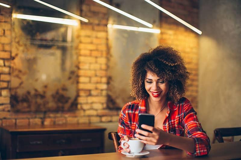 Afro-Frau, die Telefon ansieht und lächelt