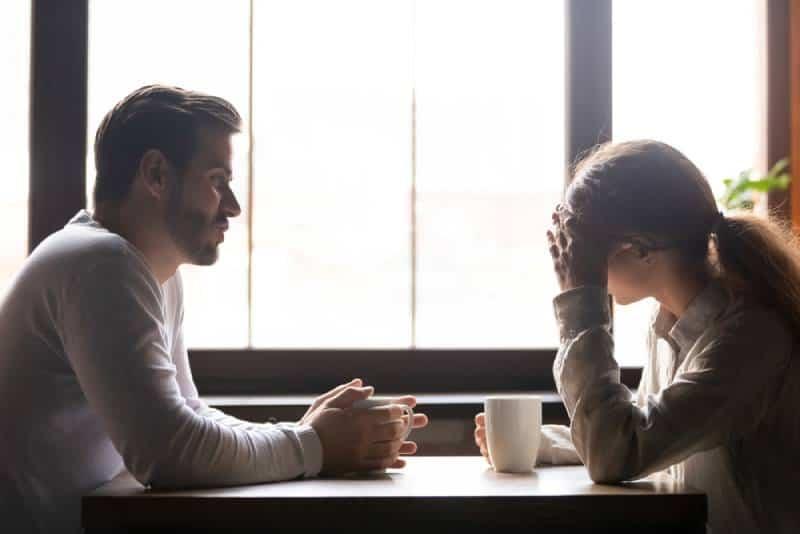 Verärgerte Frau, die mit ihrem Freund spricht, während Kaffee trinkt