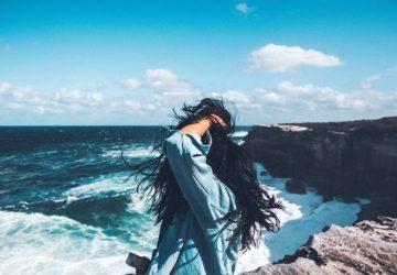 der Rücken der Frau steht am Meer