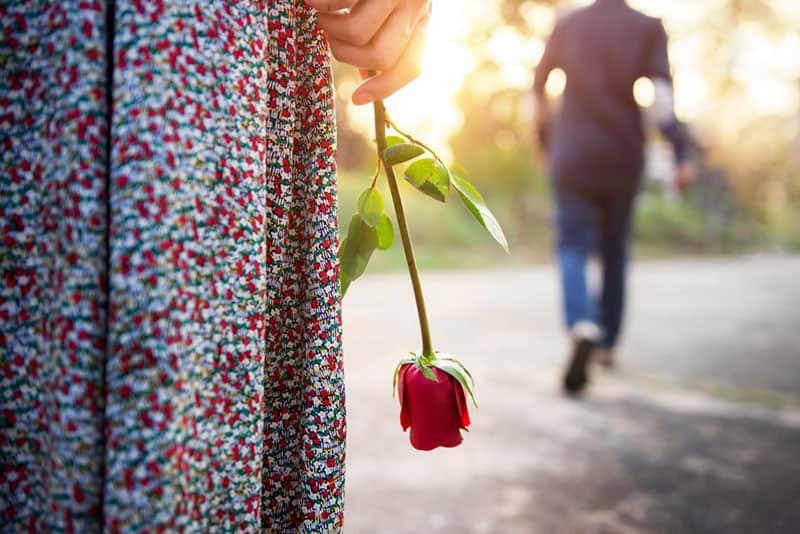Mädchen hält Rosen nieder, während Mann sie verlässt