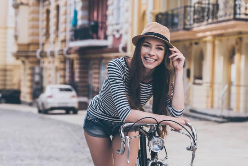 Porträt der glücklichen Frau, die draußen auf einem Fahrrad sitzt