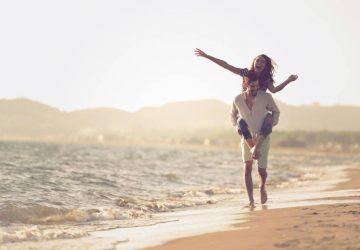 glückliches Paar huckepack am Strand am Sonnenuntergang