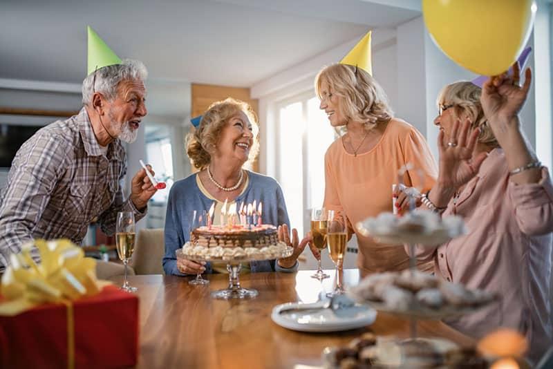 alte Leute, die Geburtstag mit Luftballons und Kuchen feiern