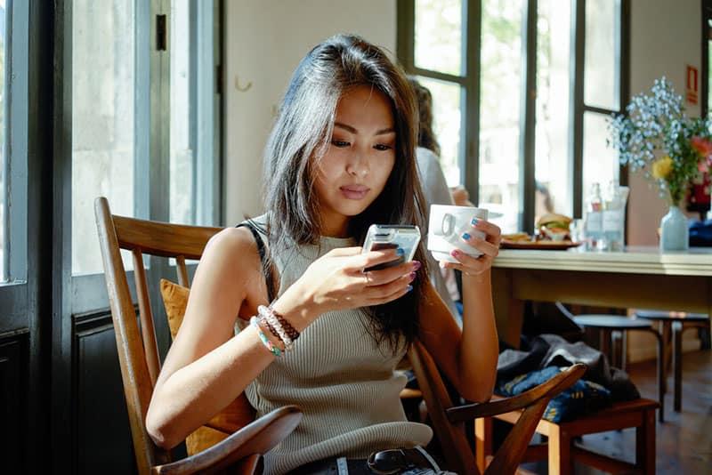 asiatische Frau, die am Telefon tippt