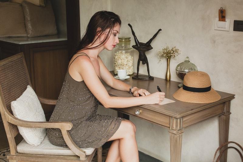 attraktive Brünette sitzt in einem Kleid auf dem Balkon und schreibt einen Brief