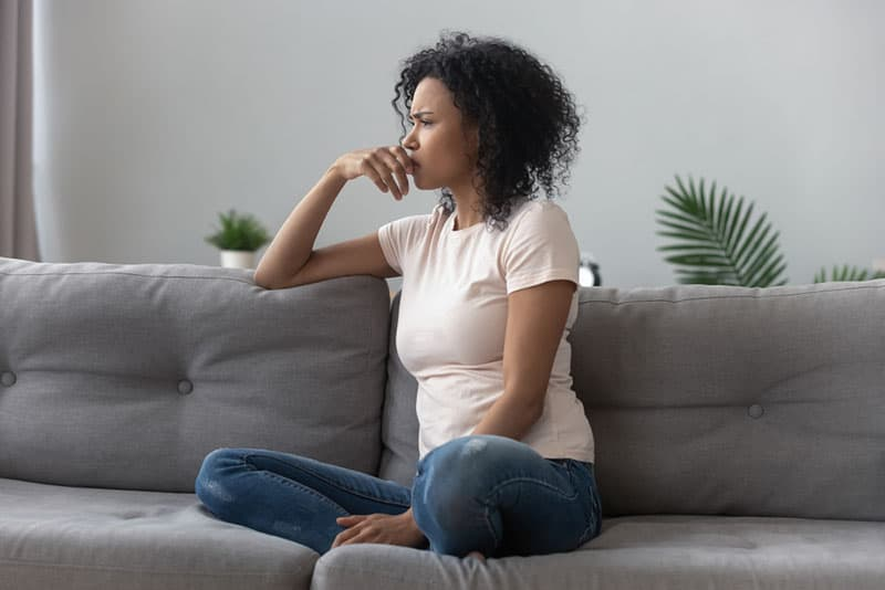 besorgte Frau sitzt auf dem Sofa