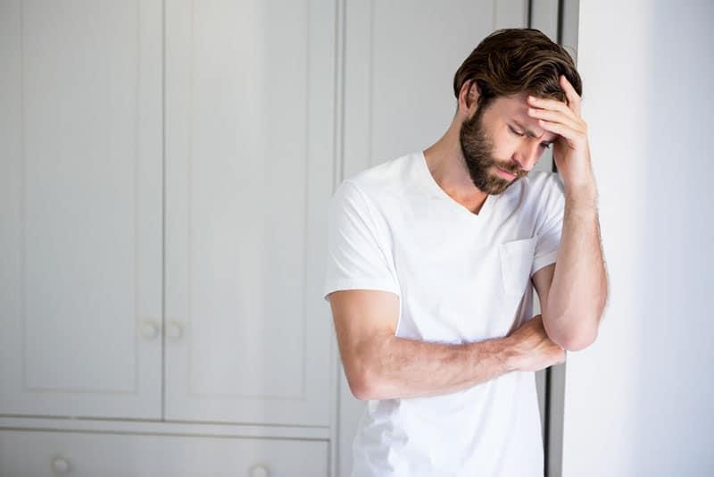 besorgter Mann an der Wand stehen