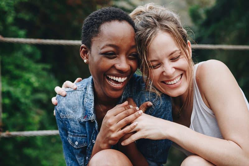 beste Freunde lächeln und umarmen sich zusammen