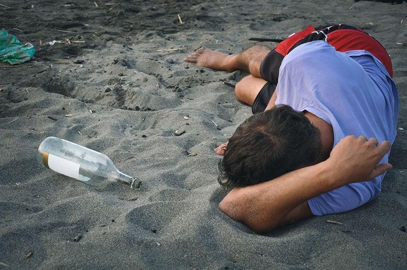 betrunkener Mann, der am Strand schläft