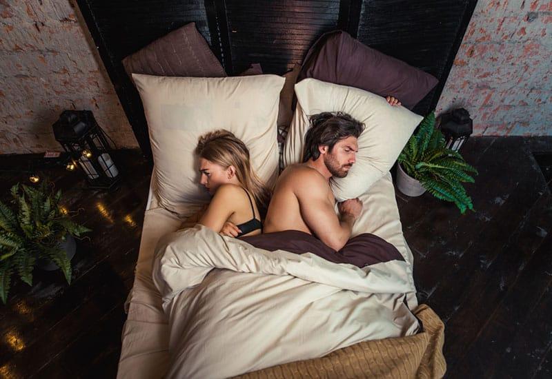 blonde Frau und Mann liegen im Schlafzimmer mit Pflanzen