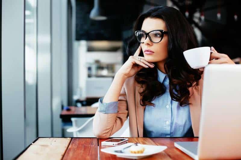denkende Frau an der Kaffeebar, die durch Fenster schaut
