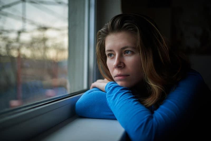 denkende Frau, die auf Fenstern sitzt und nach draußen schaut
