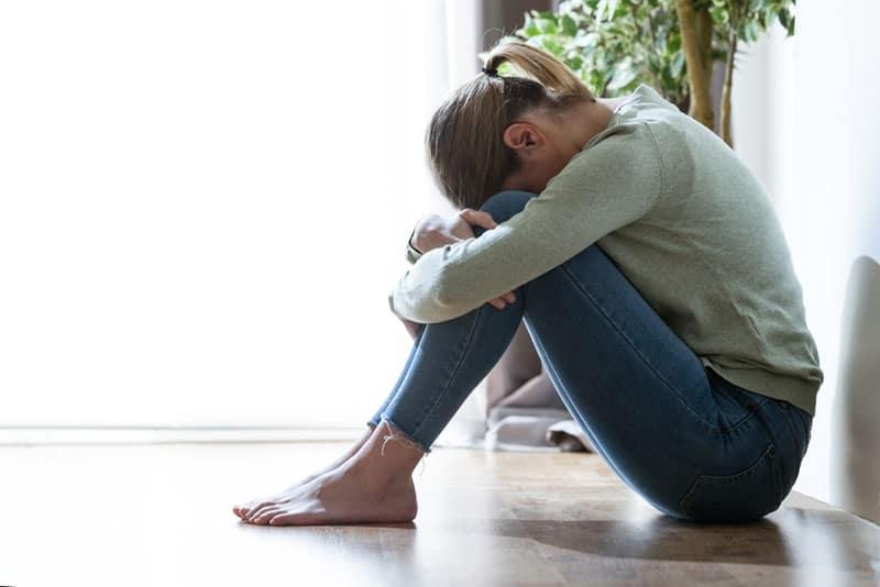 depressive Frau sitzt auf dem Boden