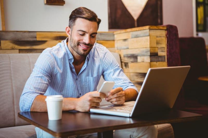 ein junger Geschäftsmann, der lächelt und eine Nachricht schreibt
