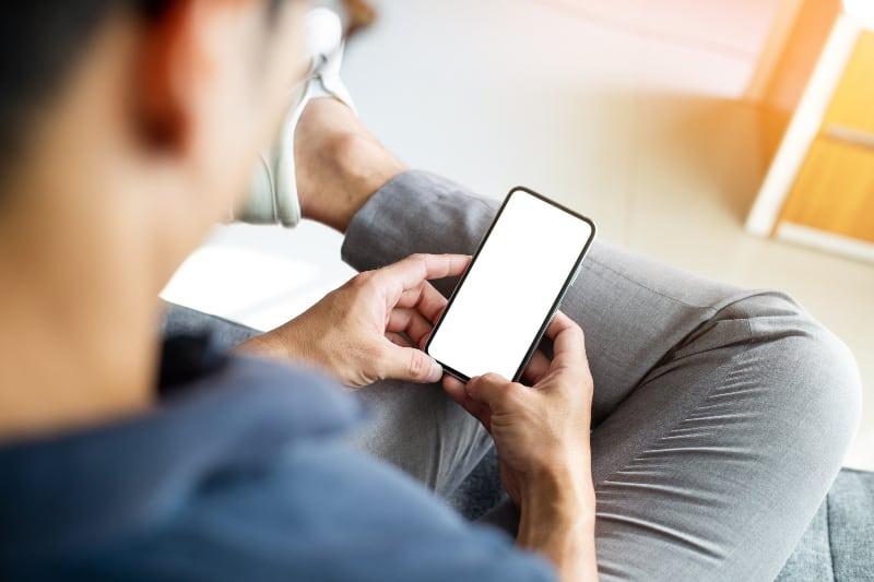 ein junger Mann, der den weißen Hintergrund seines Handys betrachtet