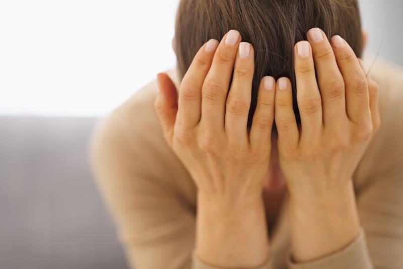 eine gestresste junge Frau, die auf der Couch sitzt