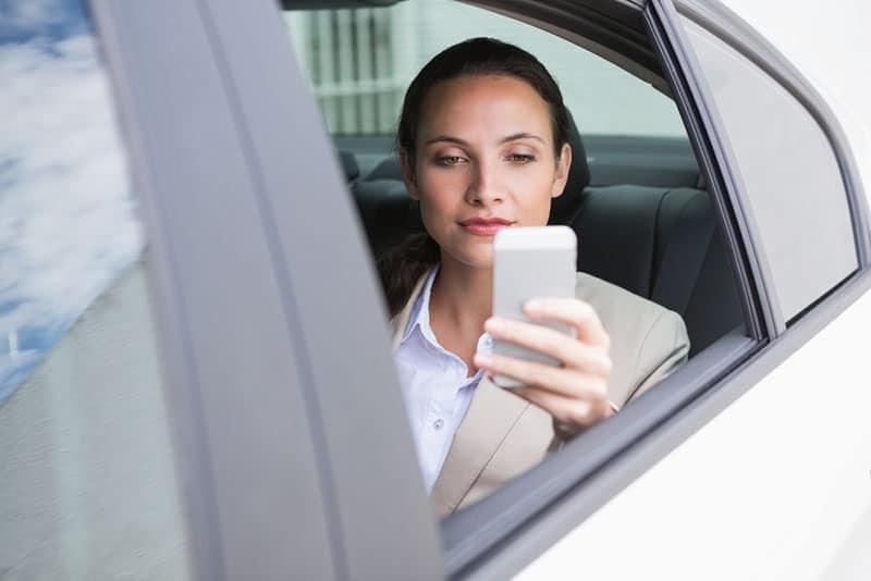 fokussierte Frau, die eine Textnachricht liest
