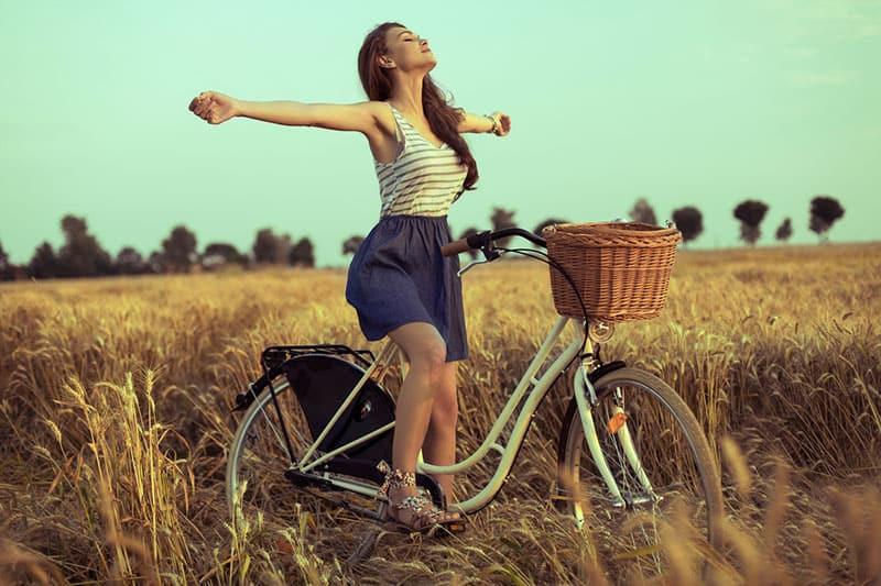 glückliche Frau auf dem Fahrrad im Feld